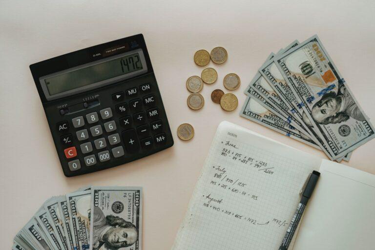 Imagem de notas de dinheiro e moderas em uma mesa, com uma calculadora e um caderno de anotações. Imagem ilustrativa texto franquias 200 mil.