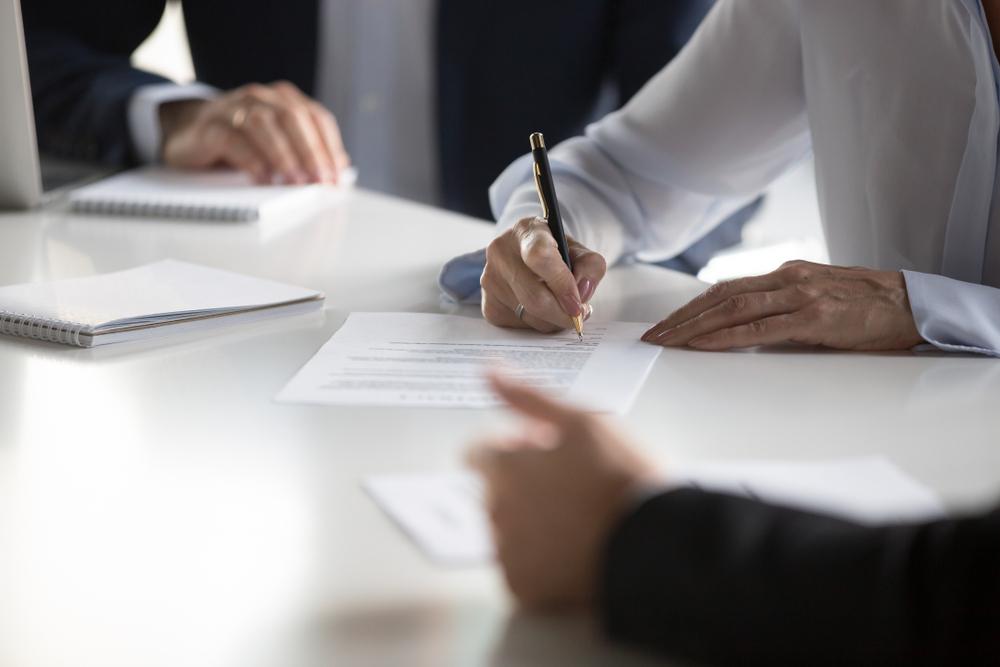 Vemos um homem assinando contrato com dois empresários ao fundo (imagem ilustrativa). Texto: franquias baratas 2021.