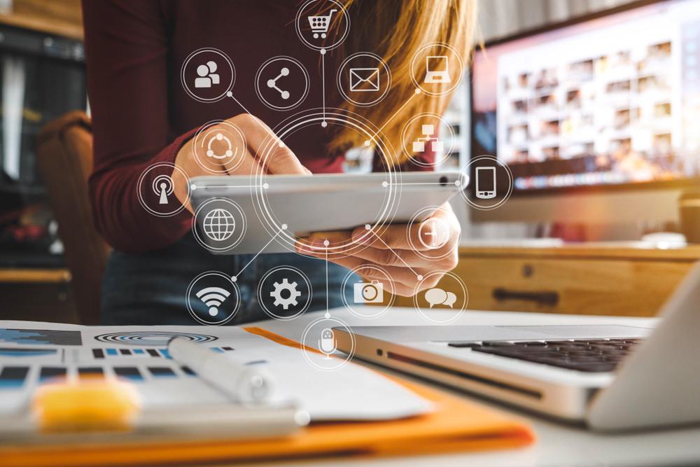 Vemos uma mulher com tablet e computador e desenhos relacionados ao marketing digital (imagem ilustrativa). Texto: franquias baratas 2021.