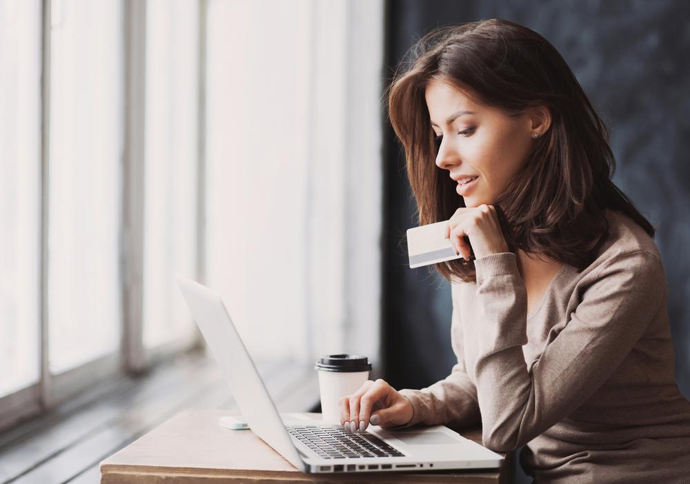 Vemos uma mulher utilizando cartão para fazer um pagamento em seu computador (imagem ilustrativa). Texto: franquias baratas 2021.
