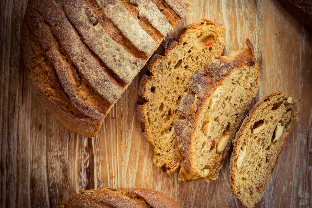 Vemos várias fatias de pão artesanal sobre uma mesa (imagem ilustrativa). Texto: franquias baratas 2021.