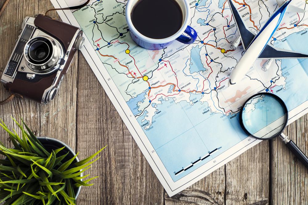 Vemos um mapa com uma xícara, avião em miniatura, lupa e câmera fotográfica por cima (imagem ilustrativa). Texto: franquias baratas 2021.