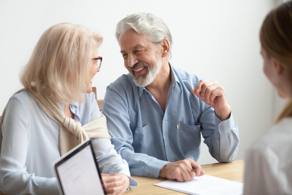 Vemos um casal de idosos conversando com uma mulher e sorrindo um para o outro (imagem ilustrativa). Texto: franquias baratas 2021.