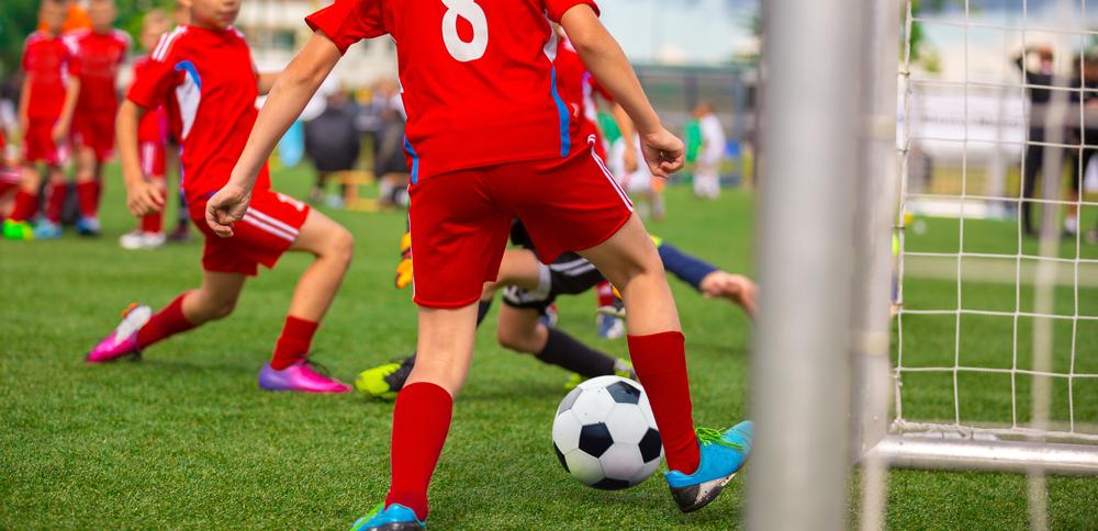 Vemos crianças jogando bola em um gramado (imagem ilustrativa). Texto: franquias baratas 2021.