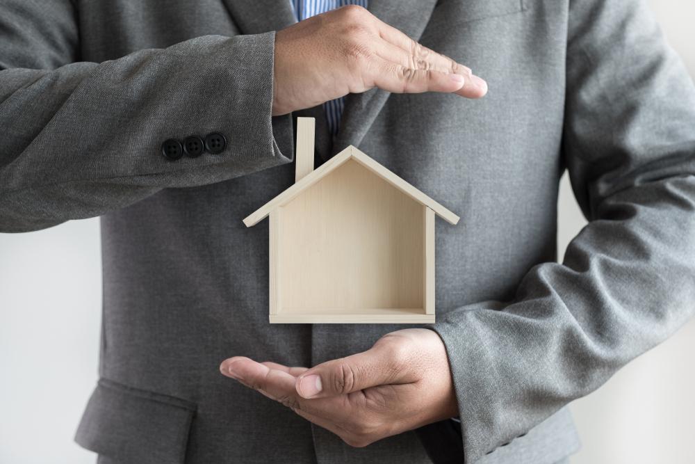 Vemos um homem de terno protegendo uma casa de madeira com suas mãos (imagem ilustrativa). Texto: franquias baratas 2021.
