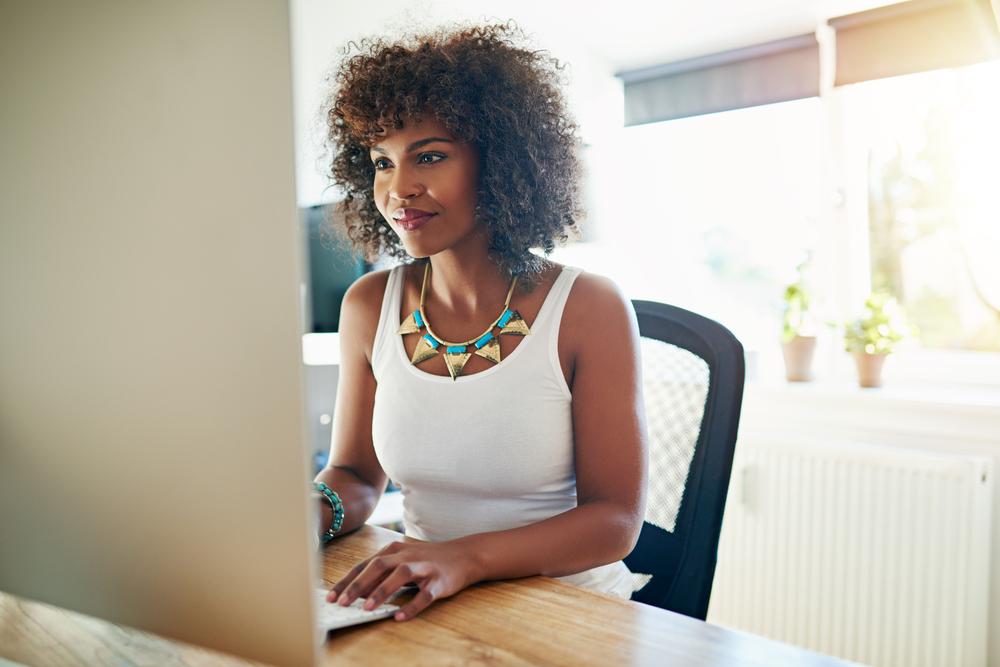 Vemos uma mulher em frente ao computador em seu escritório particular (imagem ilustrativa). Texto: franquias baratas 2021.