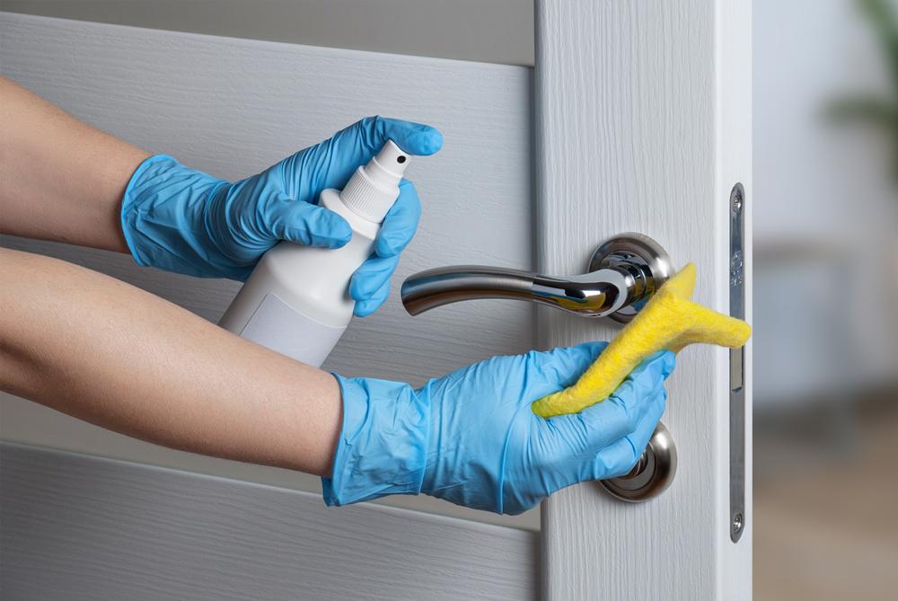Vemos uma pessoa limpando a fechadura de uma porta com pano e borrifador (imagem ilustrativa).