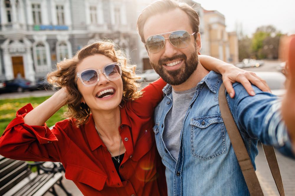 Vemos um casal tirando fotos em frente a um banco e usando óculos de sol (imagem ilustrativa).