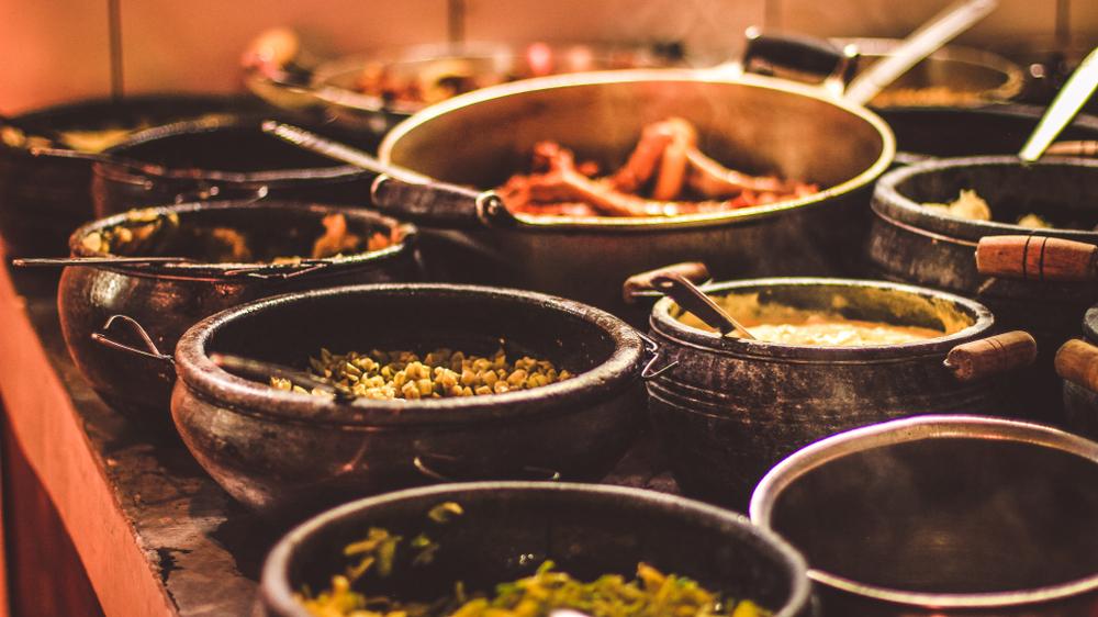 Vemos várias panelas de barro cheias de comidas típicas em um restaurante de comida mineira (imagem ilustrativa).
