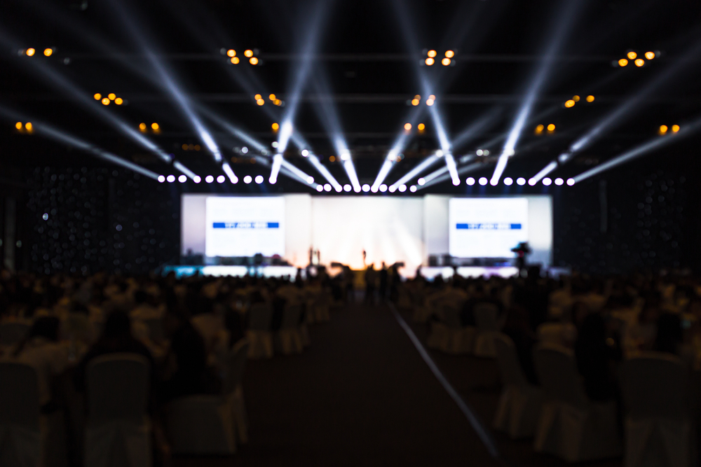 Vemos um evento, com palco iluminado, cadeiras e pessoas acompanhando (imagem ilustrativa).
