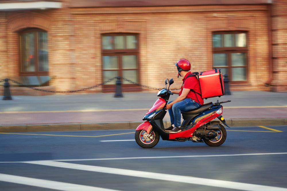 Vemos um entregador de delivery em sua moto (imagem ilustrativa). Texto: franquias baratas 2021.
