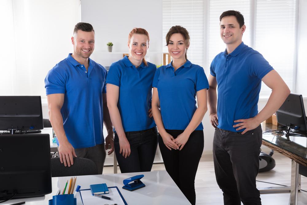 Vemos funcionários de uma empresa posando com uniforme azul (imagem ilustrativa). Texto: franquias baratas 2021.