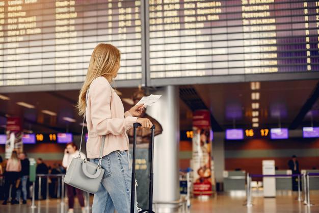 Vemos uma mulher em pé em um aeroporto, em frente ao painel de viagens, segurando a mala (imagem ilustrativa). Texto: franquias baratas 2021.