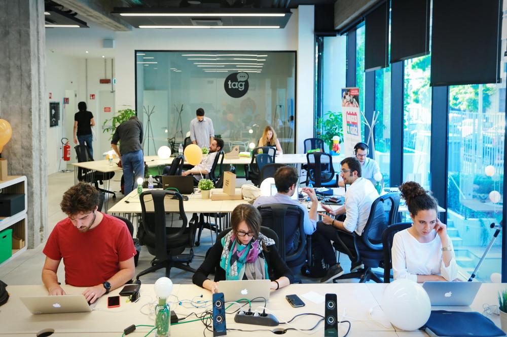 Vemos um espaço coworking com profissionais em seus computadores e em reuniões (imagem ilustrativa). Texto: franquias baratas 2021.