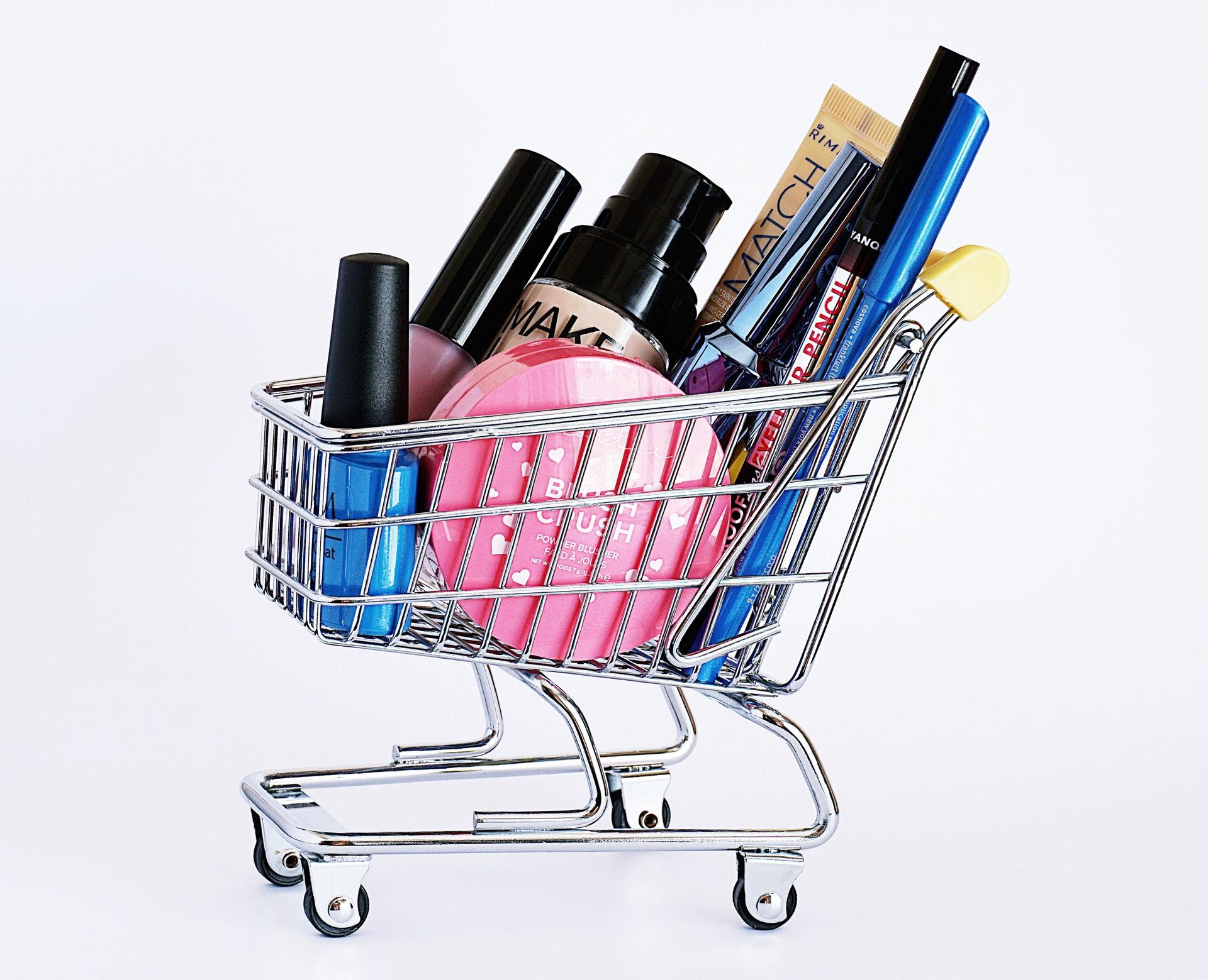Vemos diversos produtos de maquiagem em uma miniatura de carrinho de compras (imagem ilustrativa). Texto: franquias baratas e lucrativas.