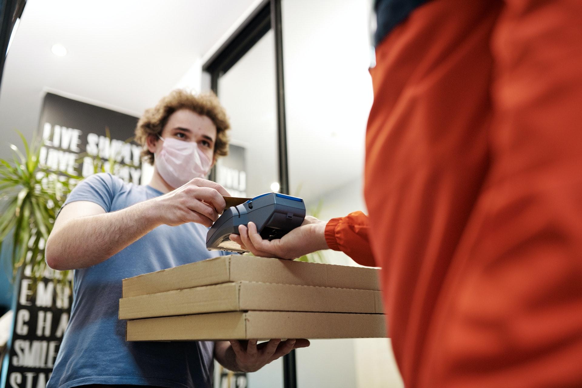 Vemos uma pessoa recebendo uma pizza em casa e passando o cartão na máquina (imagem ilustrativa).