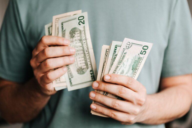 Imagem de um homem segurando notas de dólar nas mãos. imagem ilustrativa texto franquias caras.
