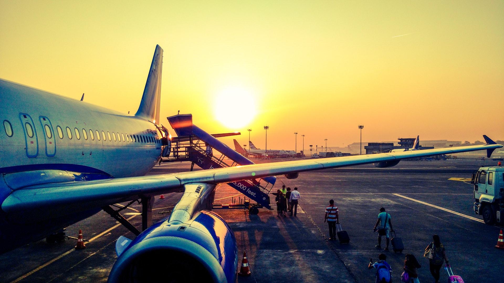 Vemos a asa de avião com o sol ao fundo (imagem ilustrativa). Texto: franquia boa e barata.