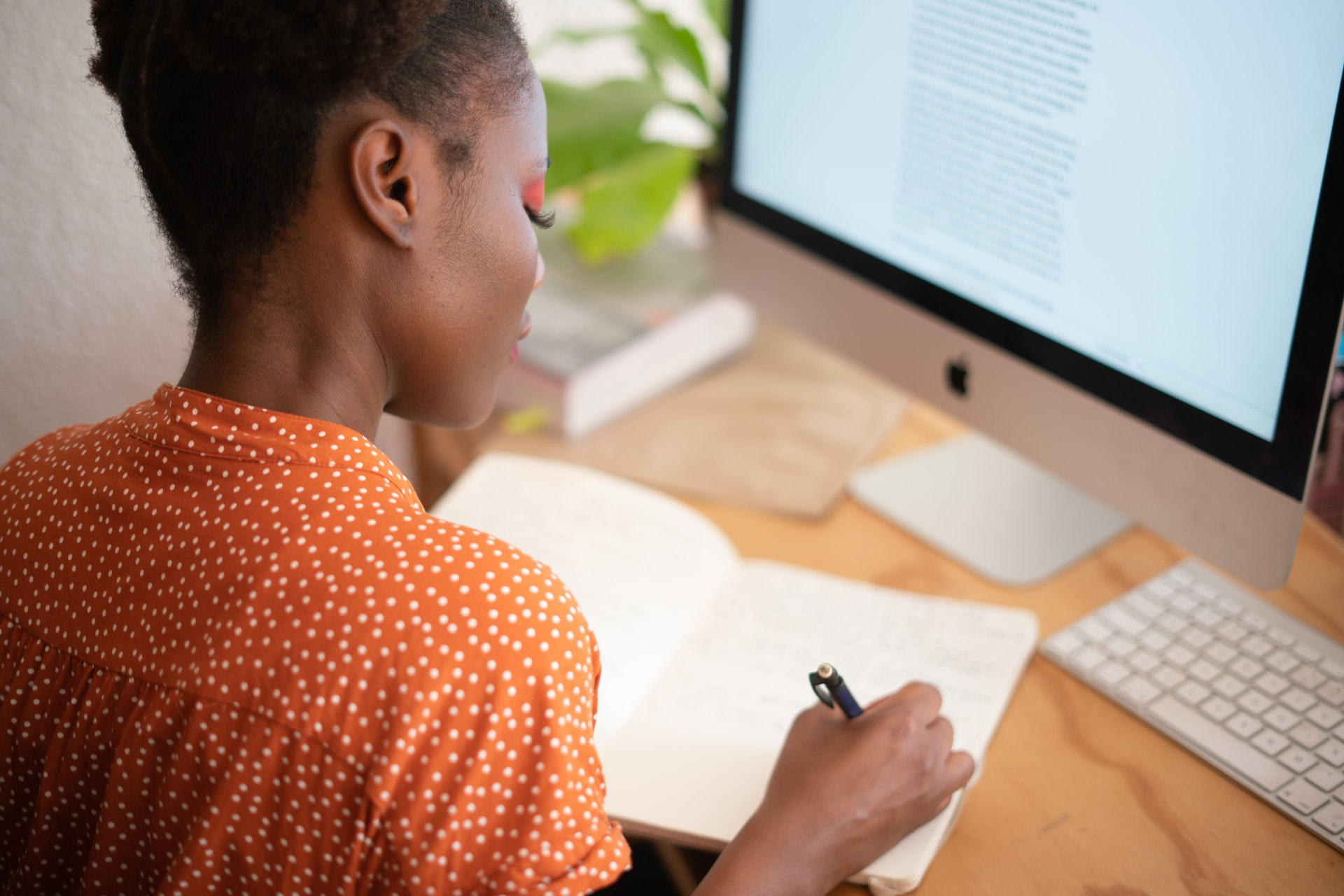 Vemos uma mulher fazendo anotações em um caderno em frente a um computador (imagem ilustrativa). Texto: franquia boa e barata.