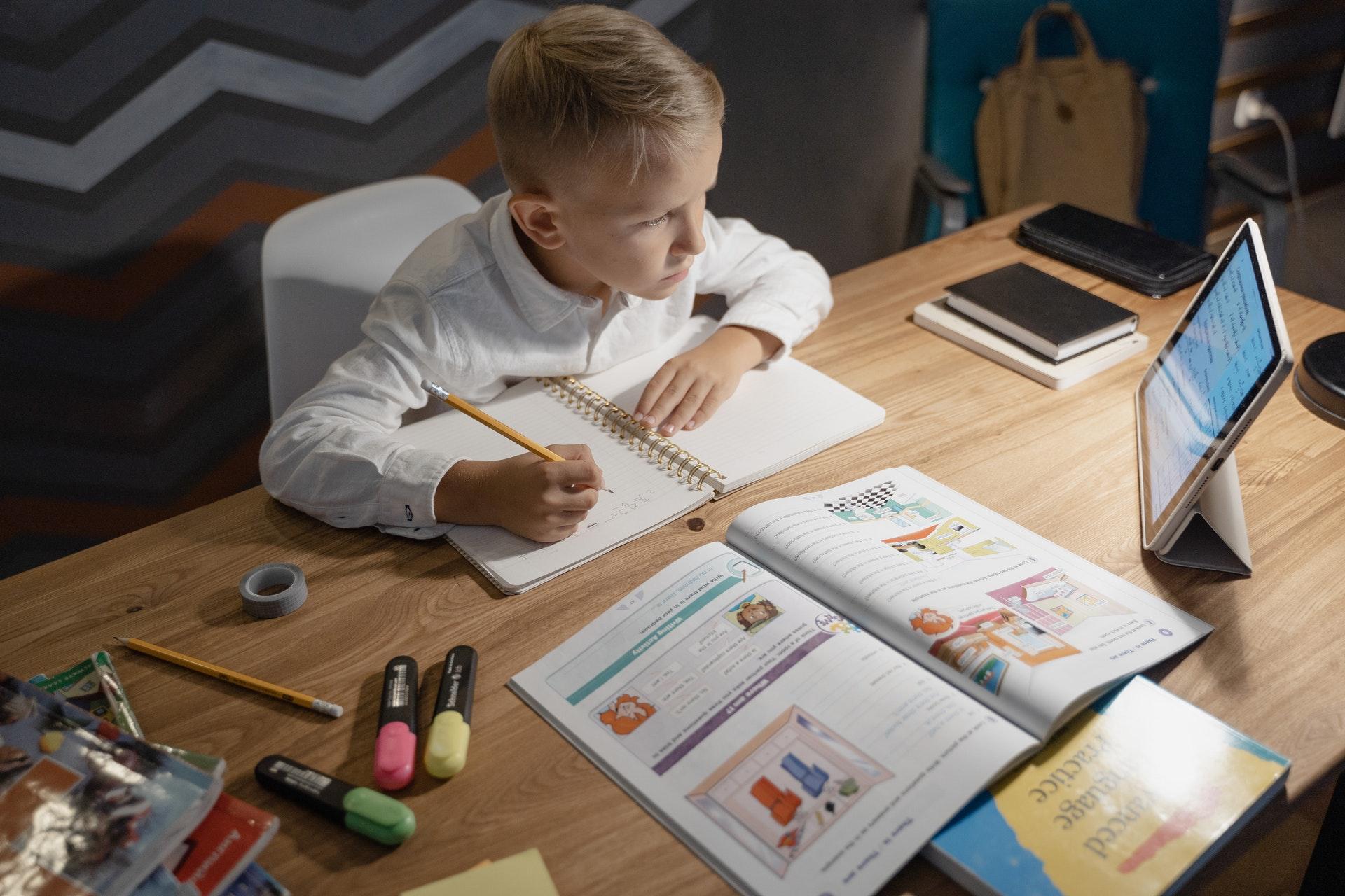 Vemos uma criança em frente um tablet enquanto estuda; vemos livros, cadernos, lápis, etc., sobre a mesa (imagem ilustrativa). Texto: franquia boa e barata.