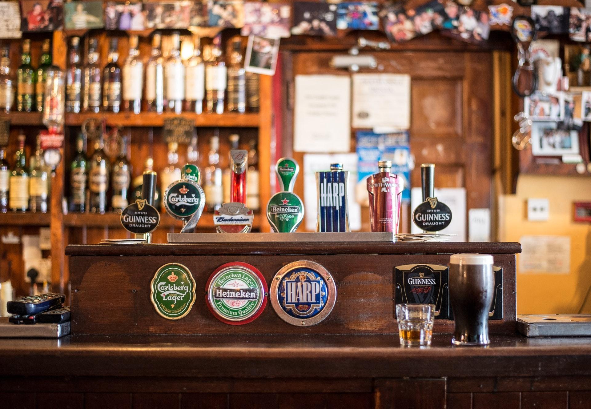 Vemos um balcão de bar com várias garrafas ao fundo (imagem ilustrativa). Texto: franquias de bares.