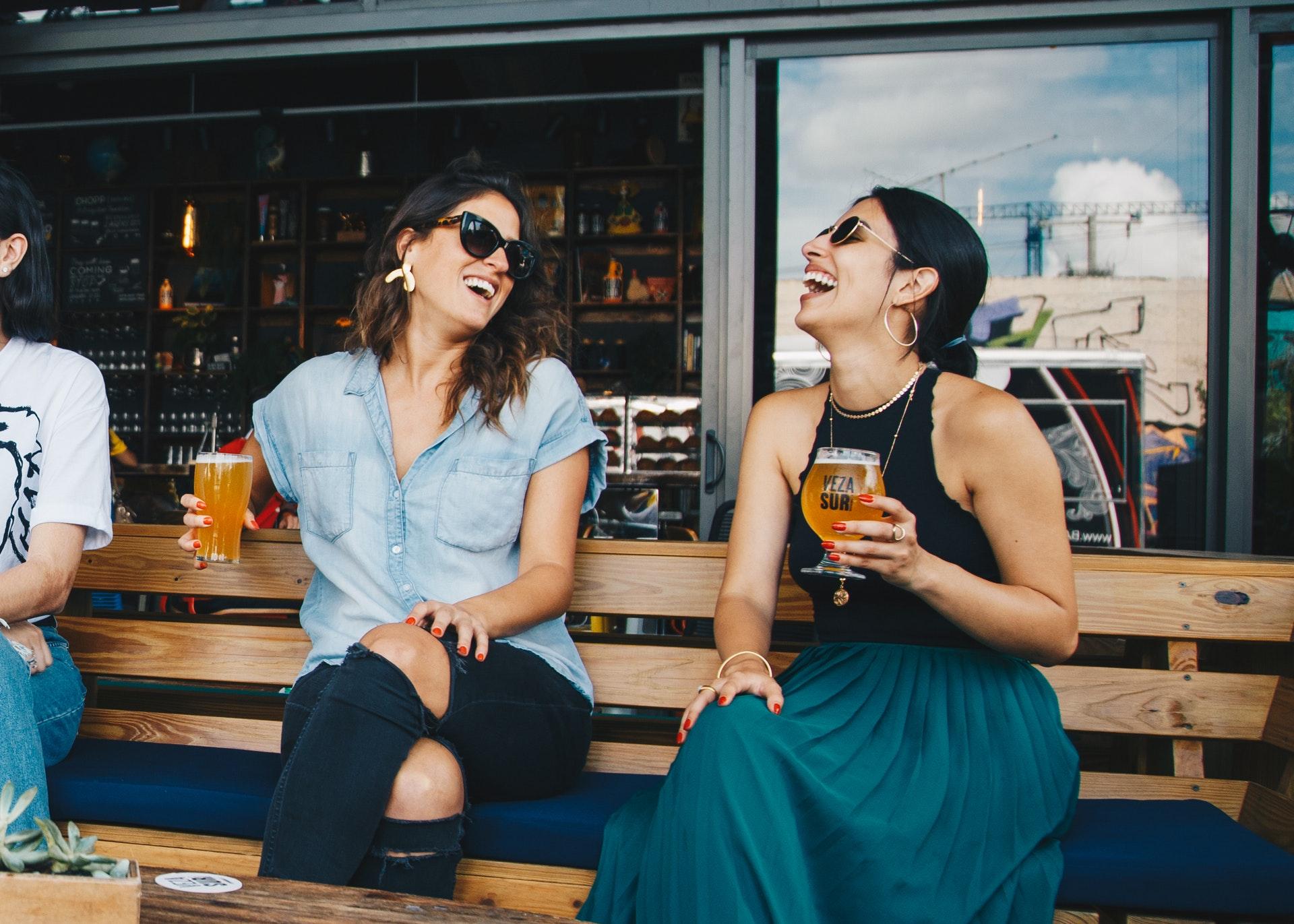 Vemos duas mulheres sorrindo enquanto seguram seus copos de cerveja (imagem ilustrativa). Texto: franquias de bares.