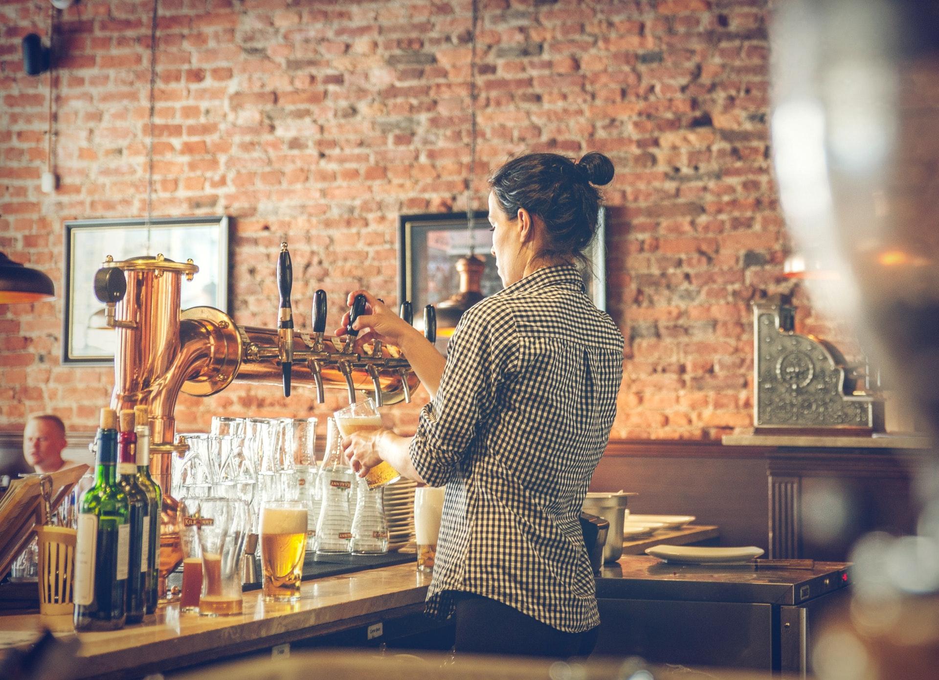 Imagem de uma atendente de bar em um balcão de chopp. Imagem ilustrativa texto franquias de bares.