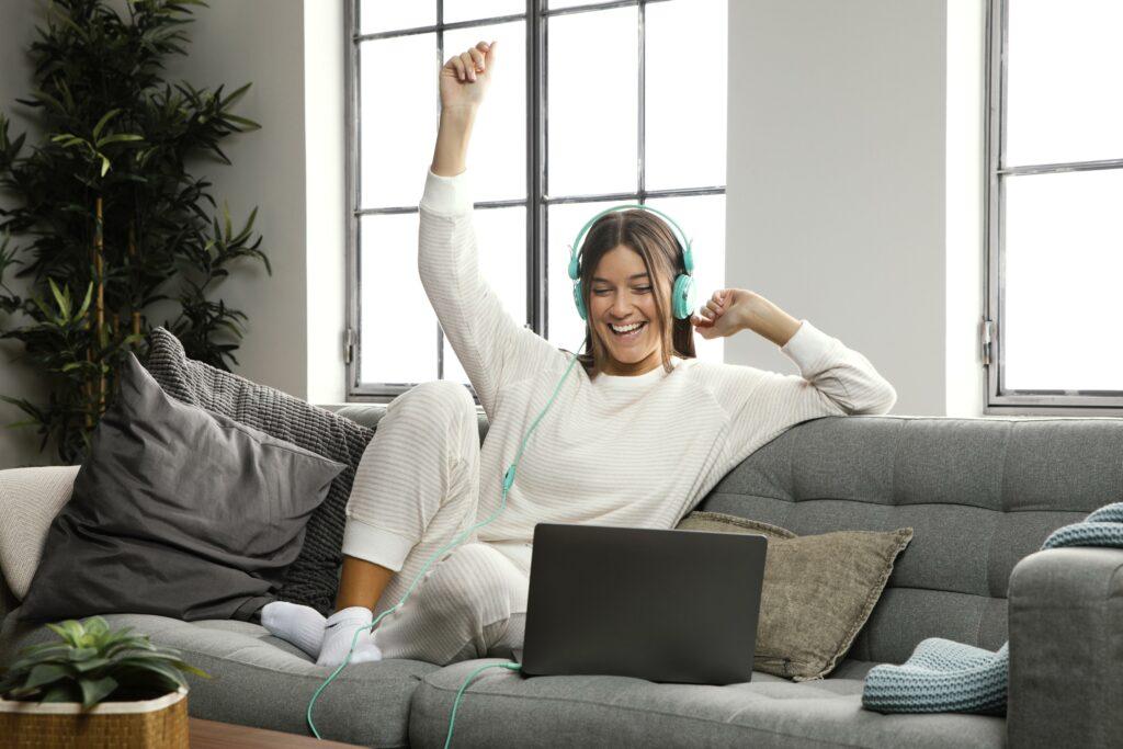 Vemos uma mulher sentada em um sofá, em frente ao computador, usando um fone de ouvido e sorrindo (imagem ilustrativa). Texto: franquias virtuais.