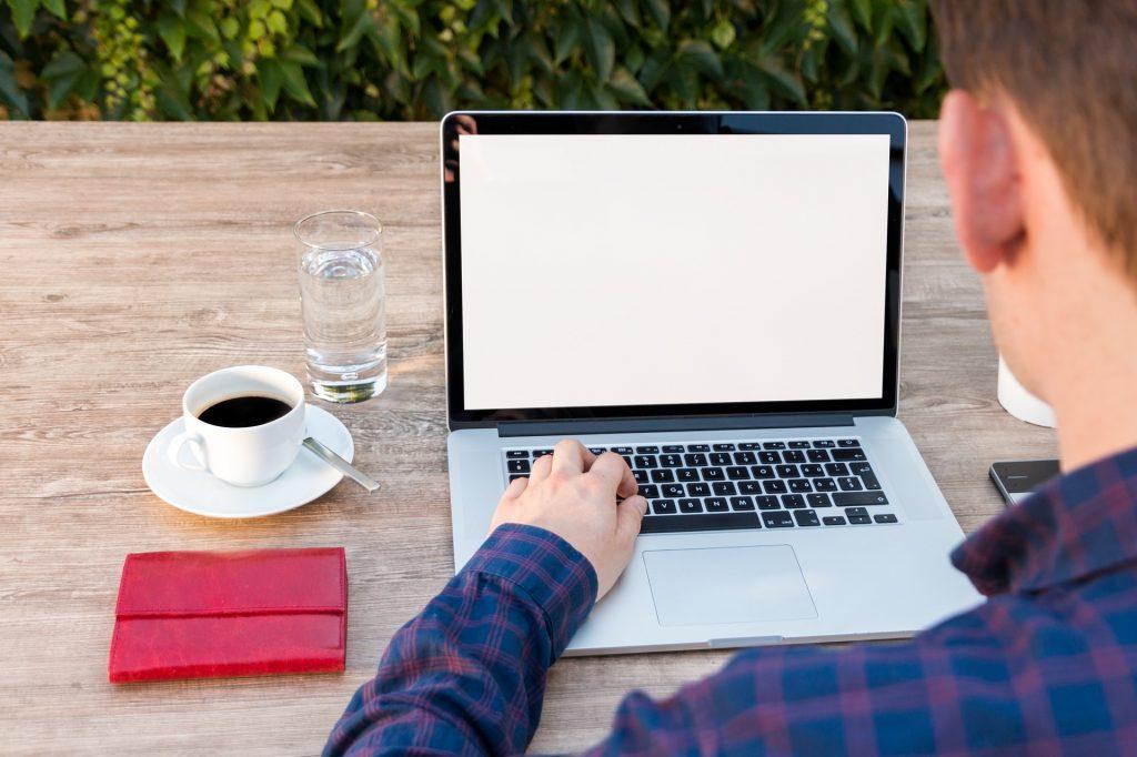 Vemos uma pessoa trabalhando em um ambiente externo. À mesa vemos computador, agenda, xícara de café, água e um celular (imagem ilustrativa). Texto: franquias virtuais.