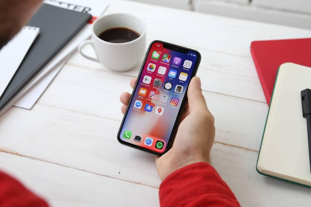 Vemos uma pessoa com celular na mão olhando sua tela inicial cheia de aplicativos (imagem ilustrativa).