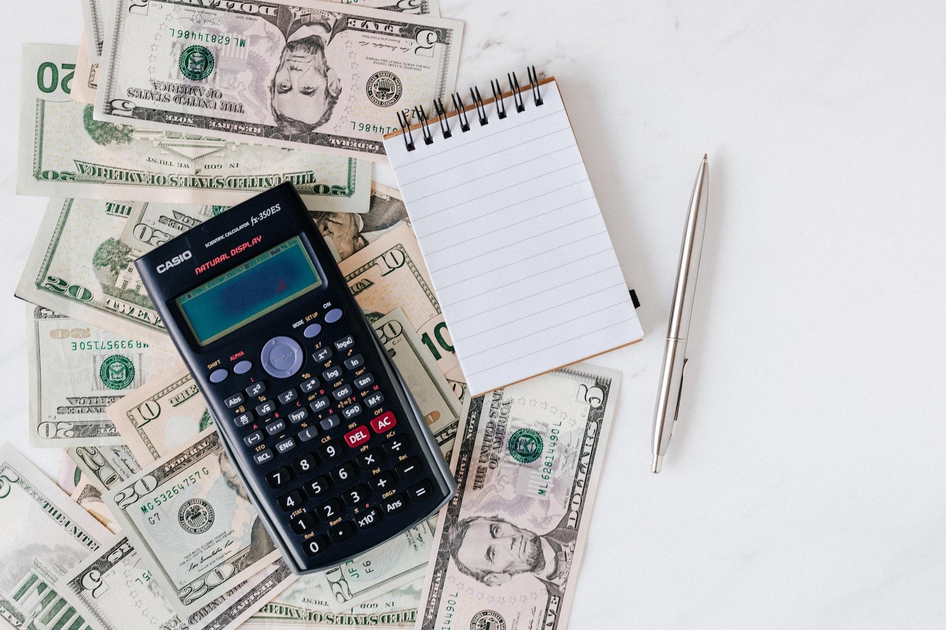 Imagem de notas de dinheiro e uma calculadora e caderno de anotações por cima. Imagem ilustrativa texto ideias de negócio.