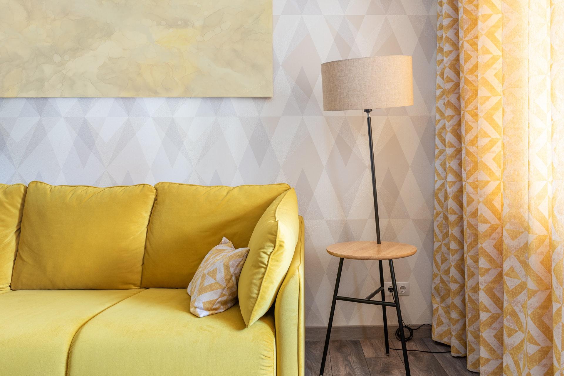 Imagem de uma parte de um sofá amarelo com uma luminária ao lado.