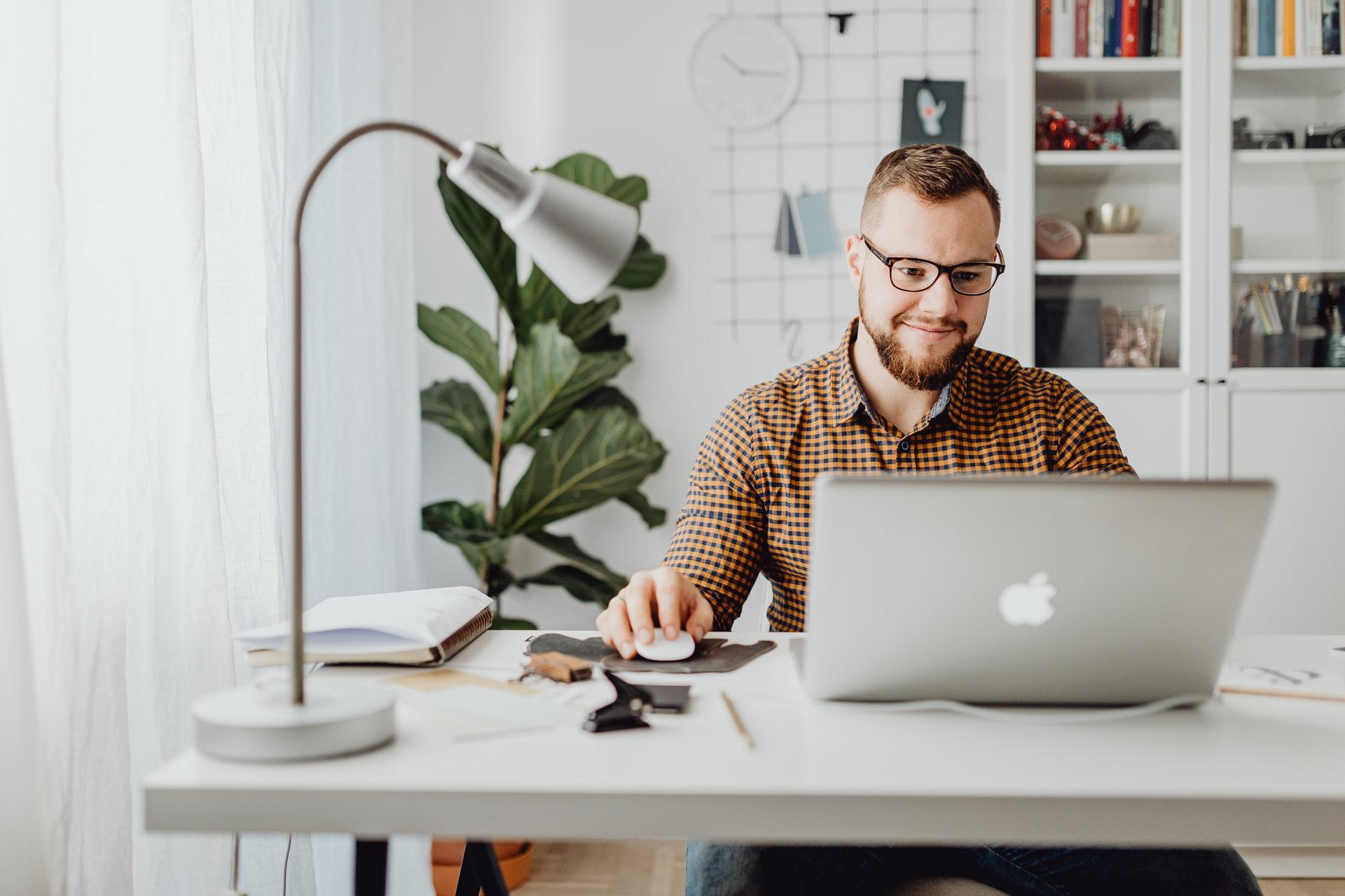 Vemos um homem, em casa, trabalhando com seu computador (imagem ilustrativa). Texto: melhores franquias de sucesso.
