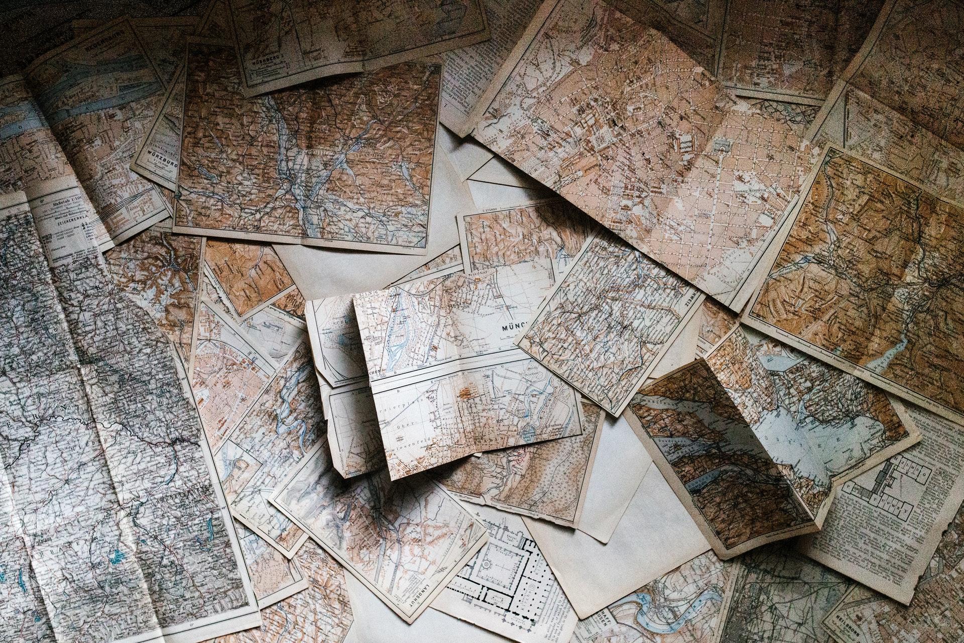 Vemos vários mapas abertos espalhados pelo chão (imagem ilustrativa). Texto: melhores franquias de sucesso.
