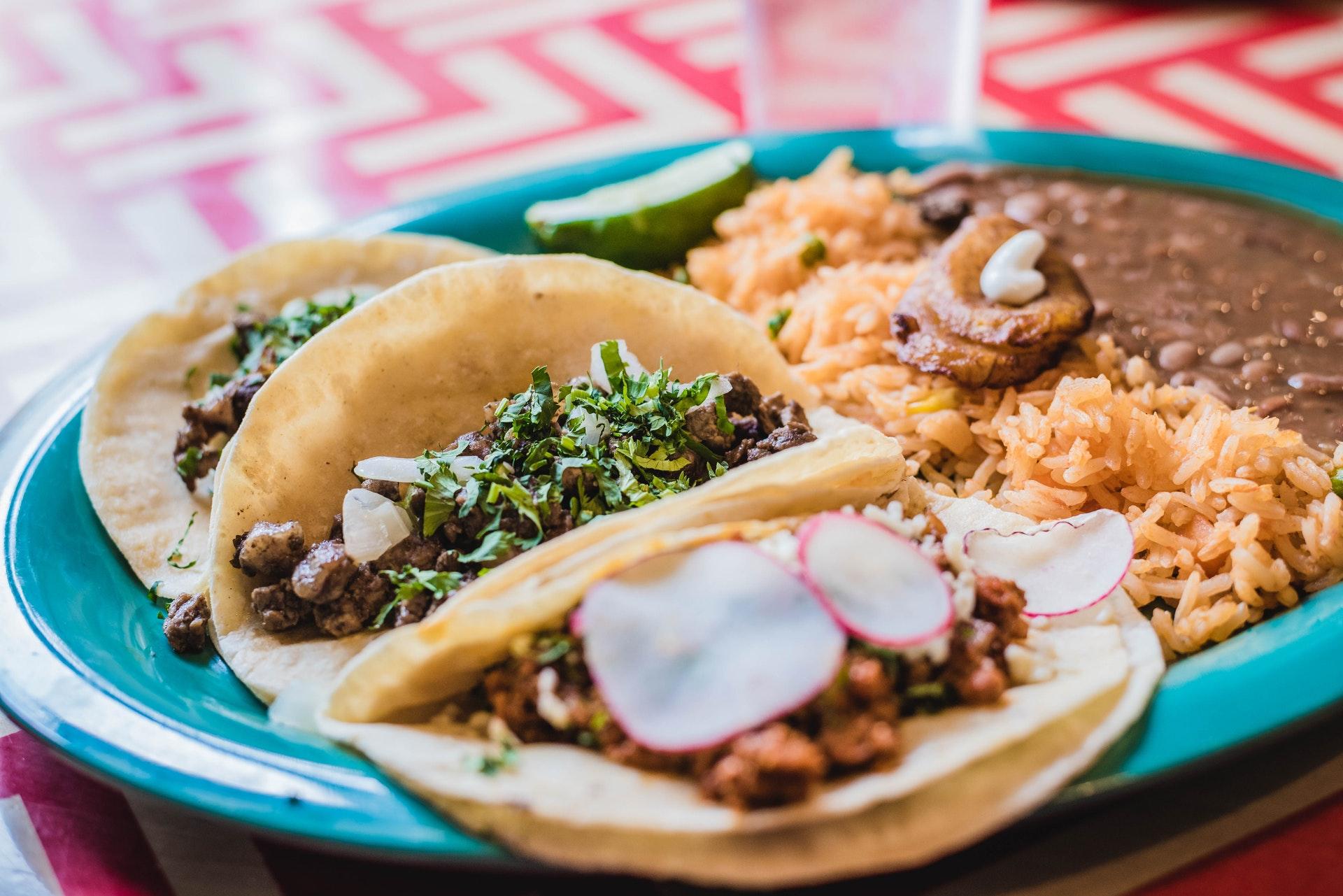 Vemos um prato de tacos mexicanos, acompanhado de chilli beans, arroz e banana frita (imagem ilustrativa). Texto: melhores franquias de sucesso.