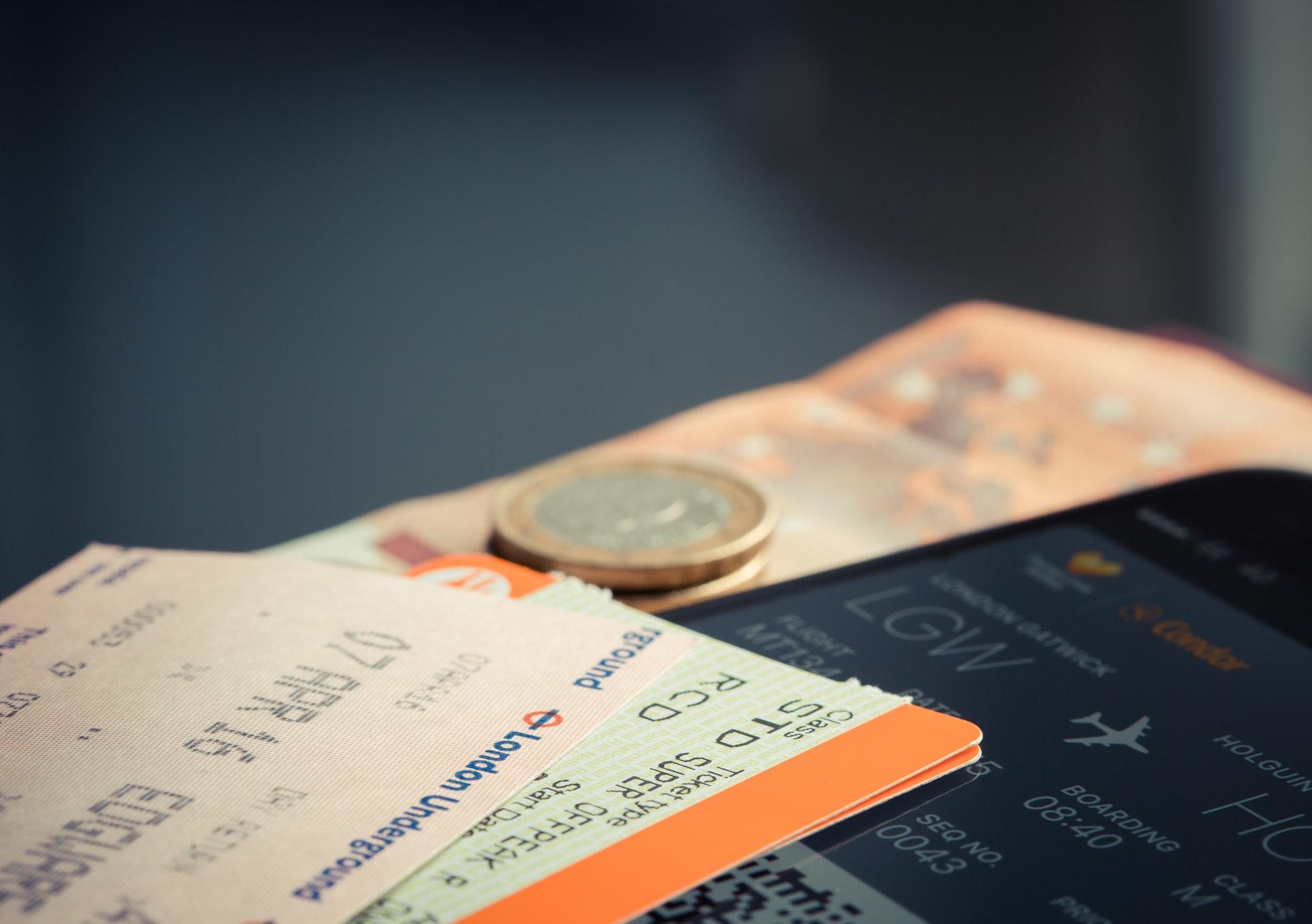 Vemos uma passagem aérea, uma nota e uma moeda sobre a tela de um celular (imagem ilustrativa). Texto: melhores franquias do momento.