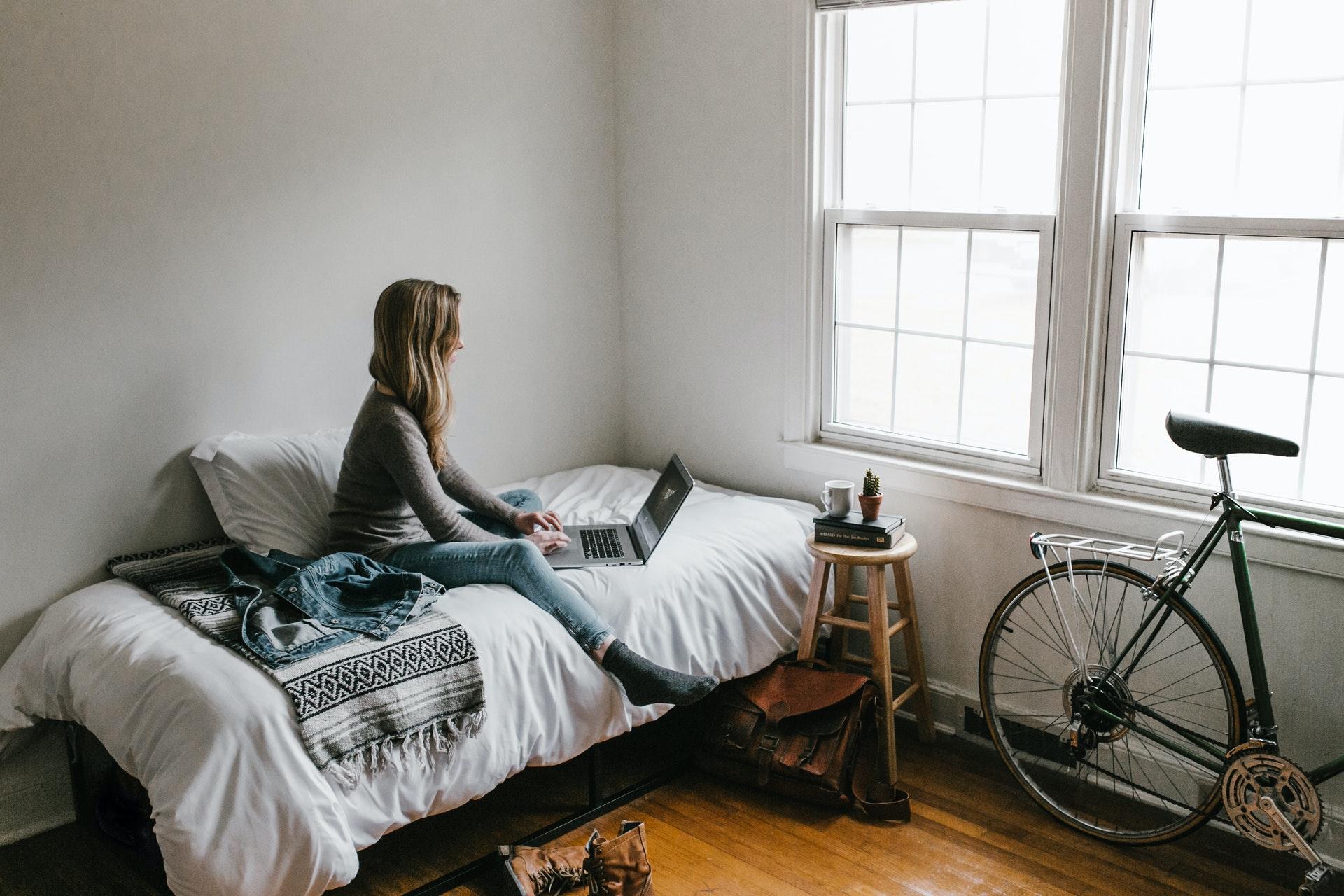 Vemos uma mulher sentada na cama olhando para o computador (imagem ilustrativa).