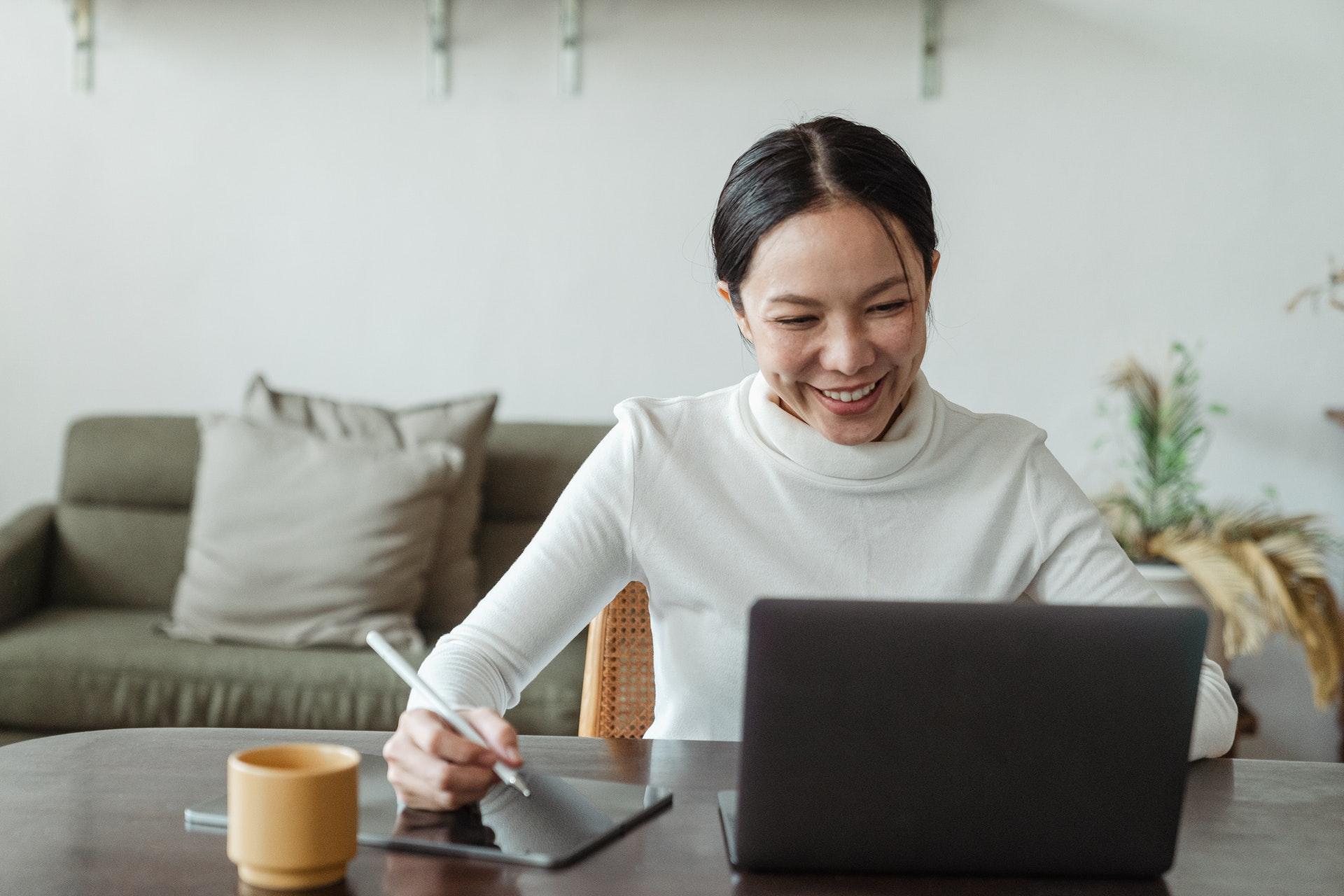 Imagem de uma mulher olhando para o computador e sorrindo. Imagem ilustrativa texto melhores franquias para investir.