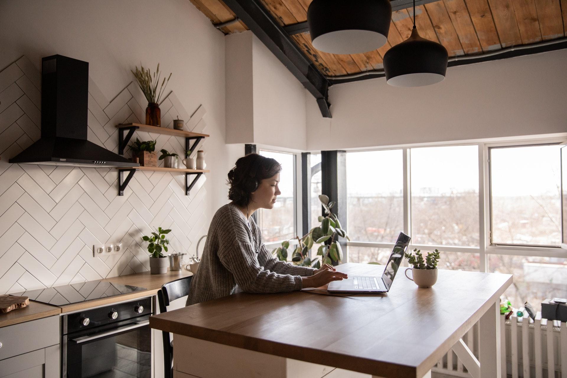 Vemos uma mulher trabalhando na cozinha de casa (imagem ilustrativa). Texto: melhores negócios home office.