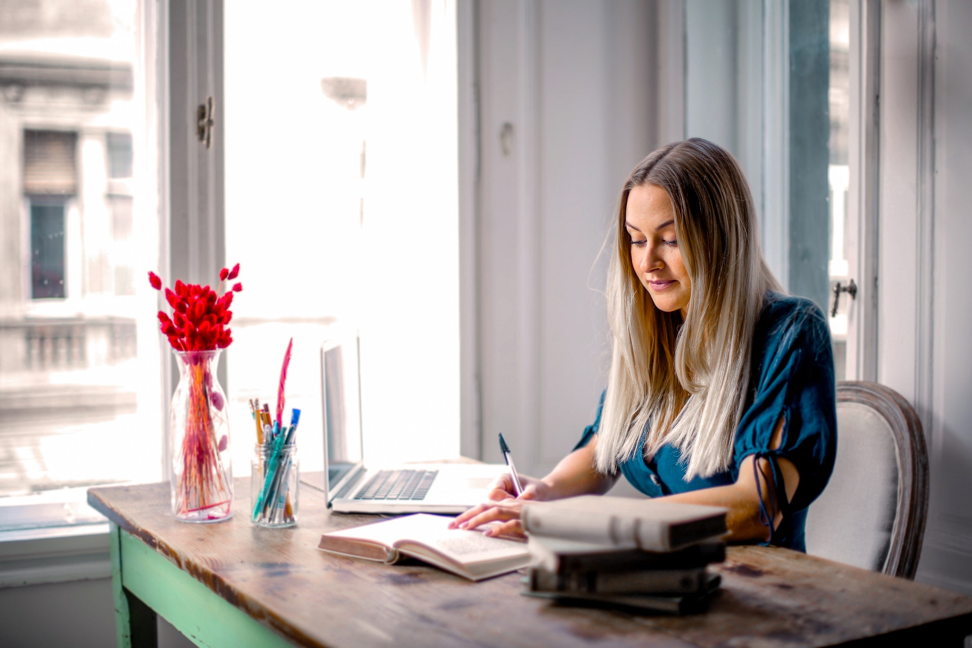Vemos uma mulher em uma mesa de escritório, em casa, enquanto realiza algumas anotações (imagem ilustrativa). Texto: melhores negócios home office.