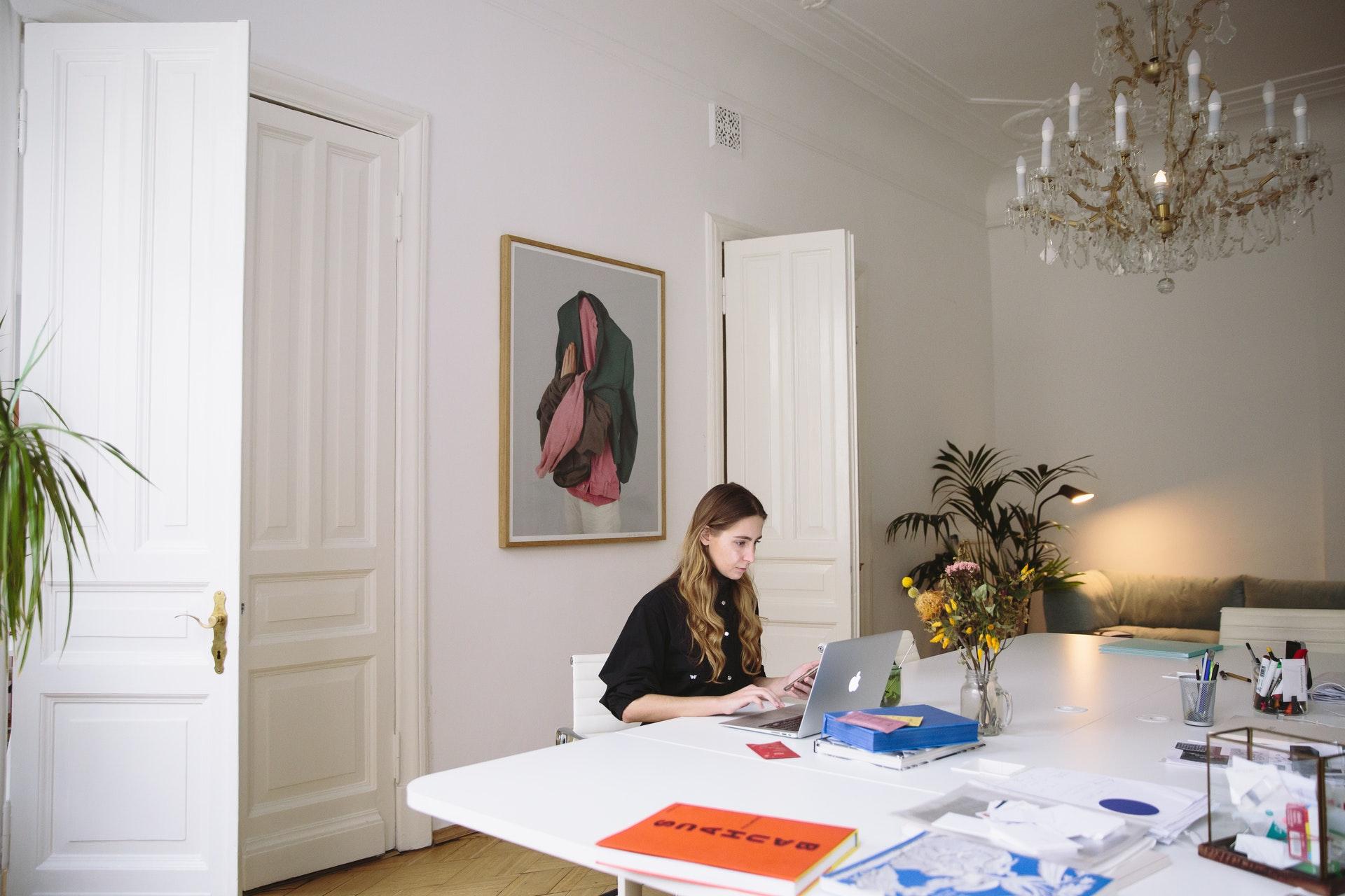 Vemos uma mulher trabalhando em um computador na sala de casa (imagem ilustrativa).