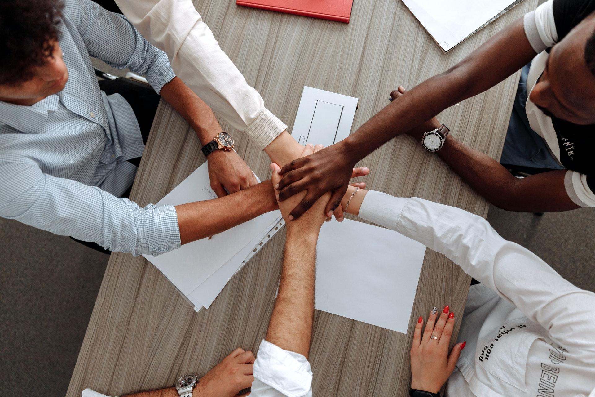 Vemos várias pessoas ao redor de uma mesa dando as mão em sinal de união (imagem ilustrativa). Texto: mulheres empreendedoras.