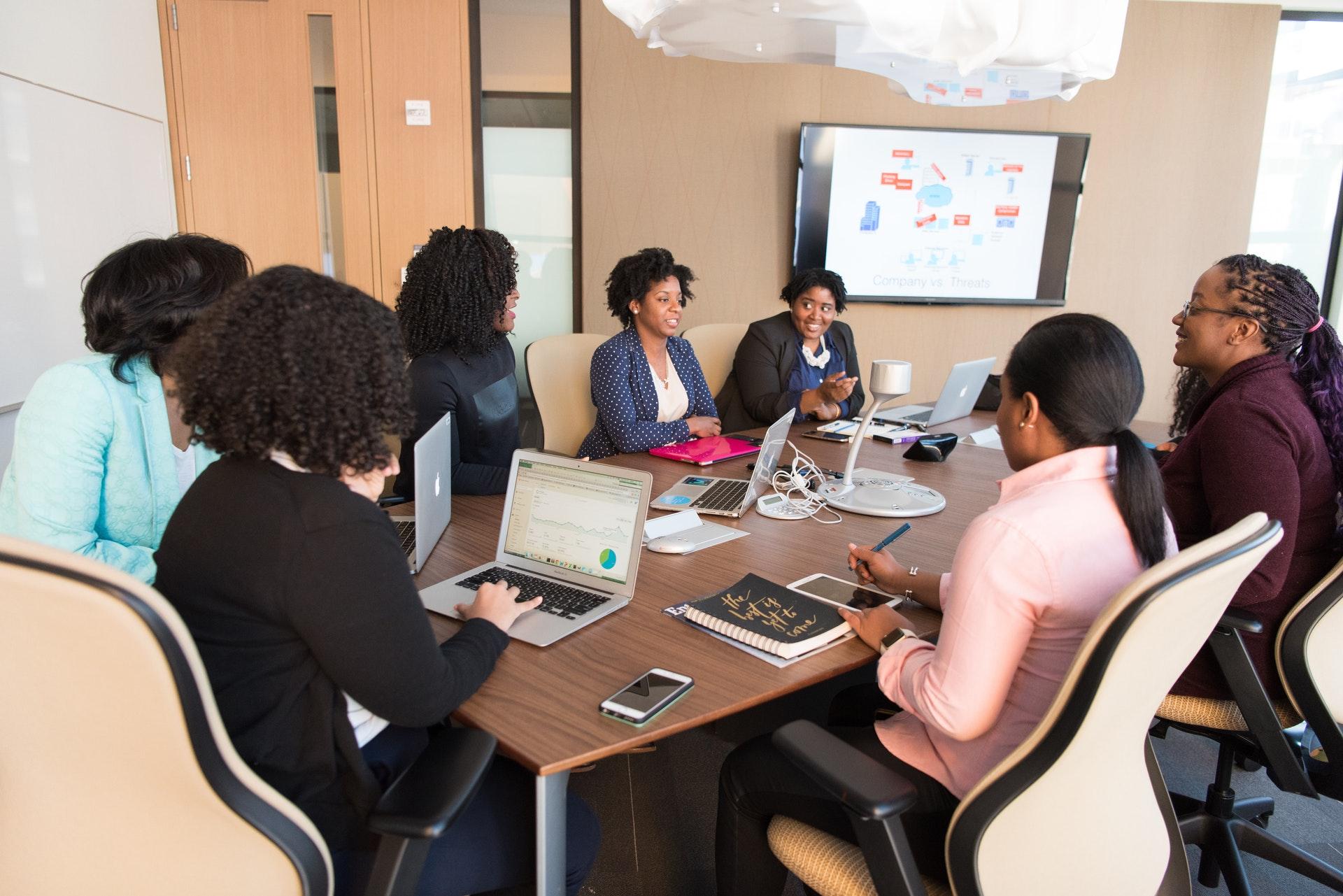 Vemos várias mulheres em uma mesa de reunião (imagem ilustrativa). Texto: mulheres empreendedoras.
