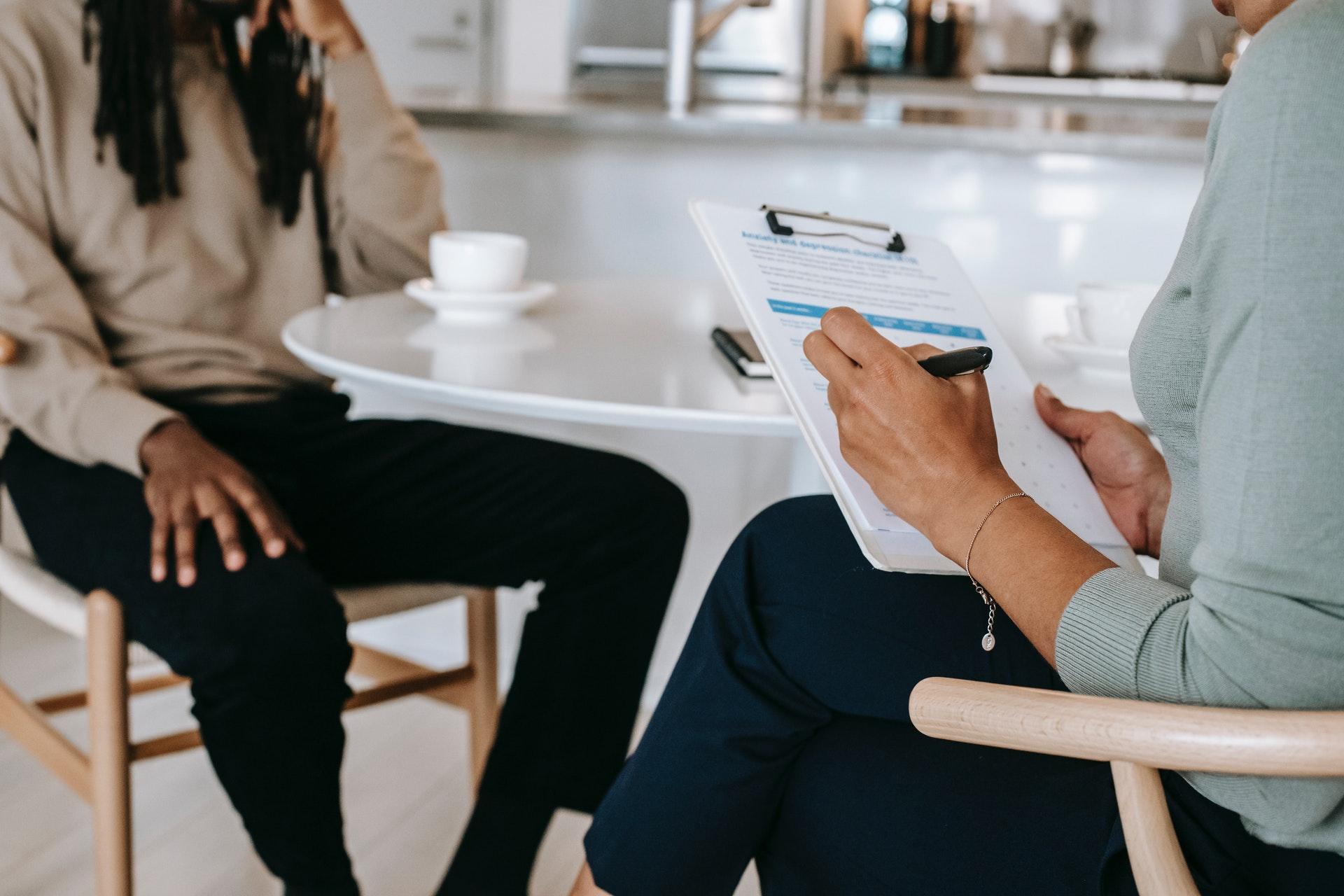 Vemos uma pessoa sentada em frente outra; uma delas preenche um papel em uma prancheta (imagem ilustrativa). Texto: negócios baratos e lucrativos.