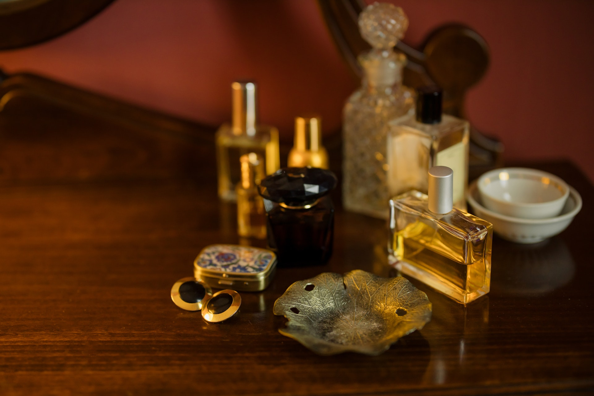 Vemos alguns vidros de perfume de diferentes tamanho sobre uma mesa de madeira (imagem ilustrativa).