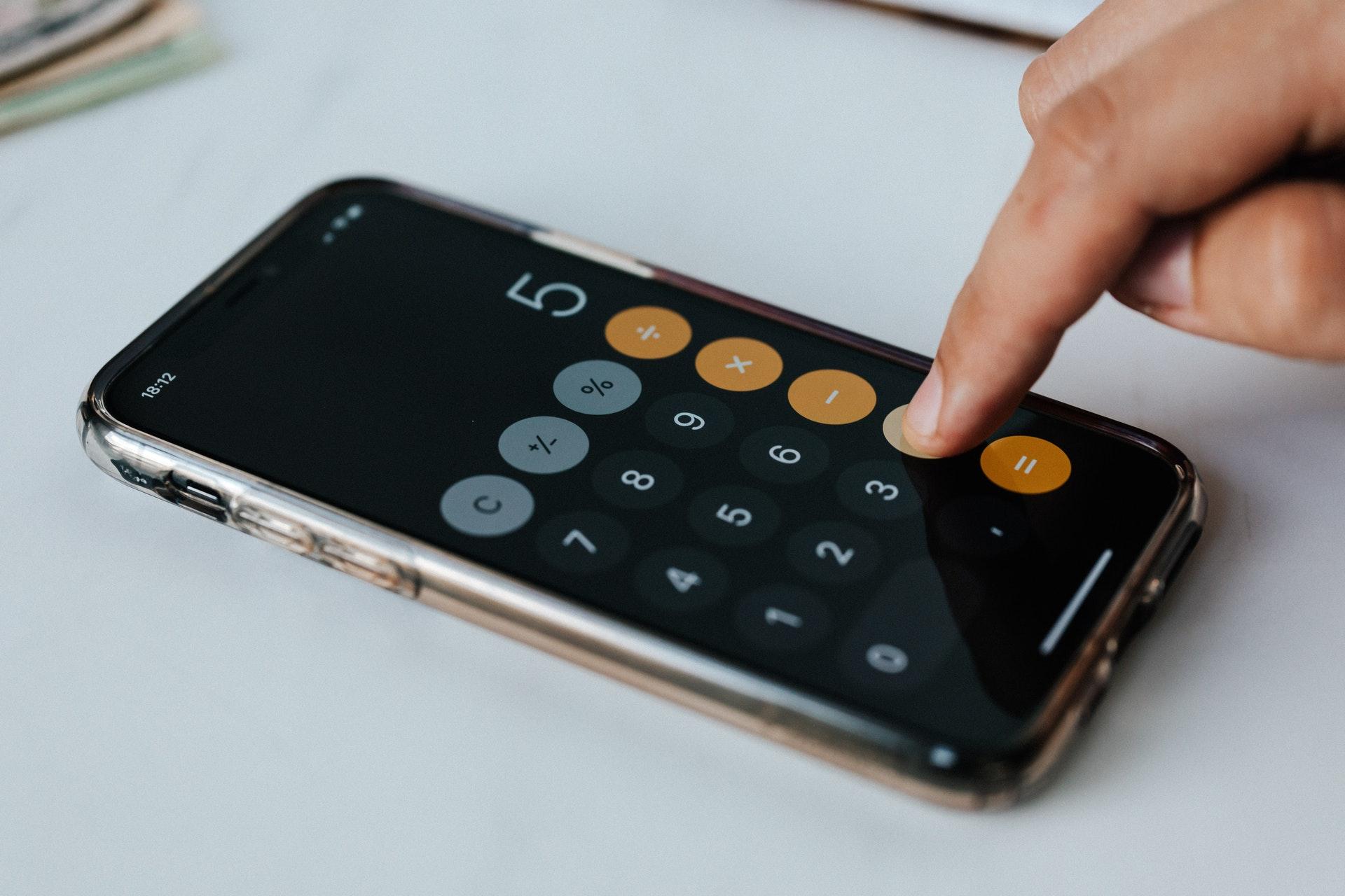 Imagem de um celular com uma calculadora na tela e uma pessoa apertando a tela. Imagem ilustrativa texto negócios baratos e lucrativos.