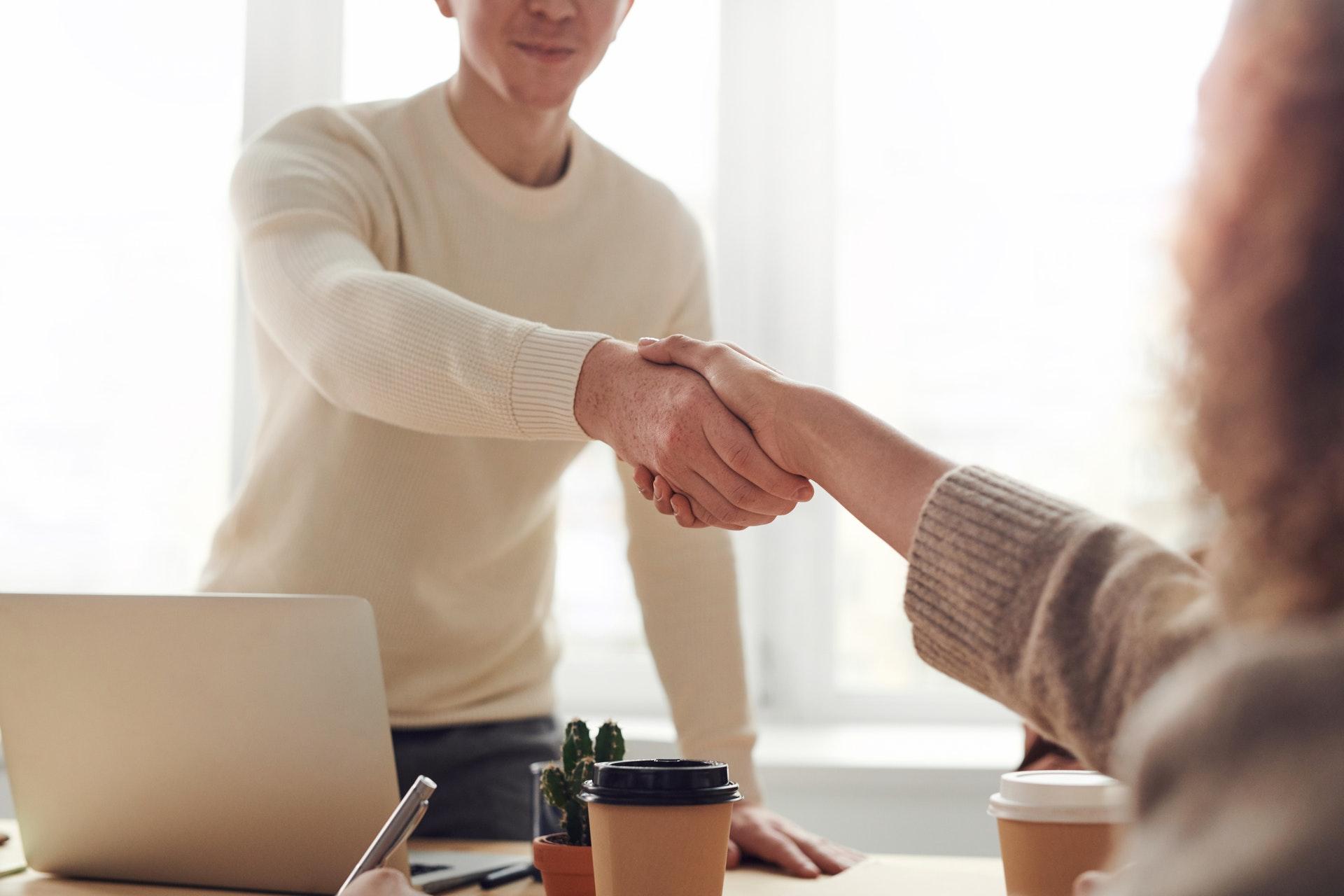 Vemos uma pessoa apertando a mão de outra (imagem ilustrativa). Texto: negócios lucrativos com pouco dinheiro.