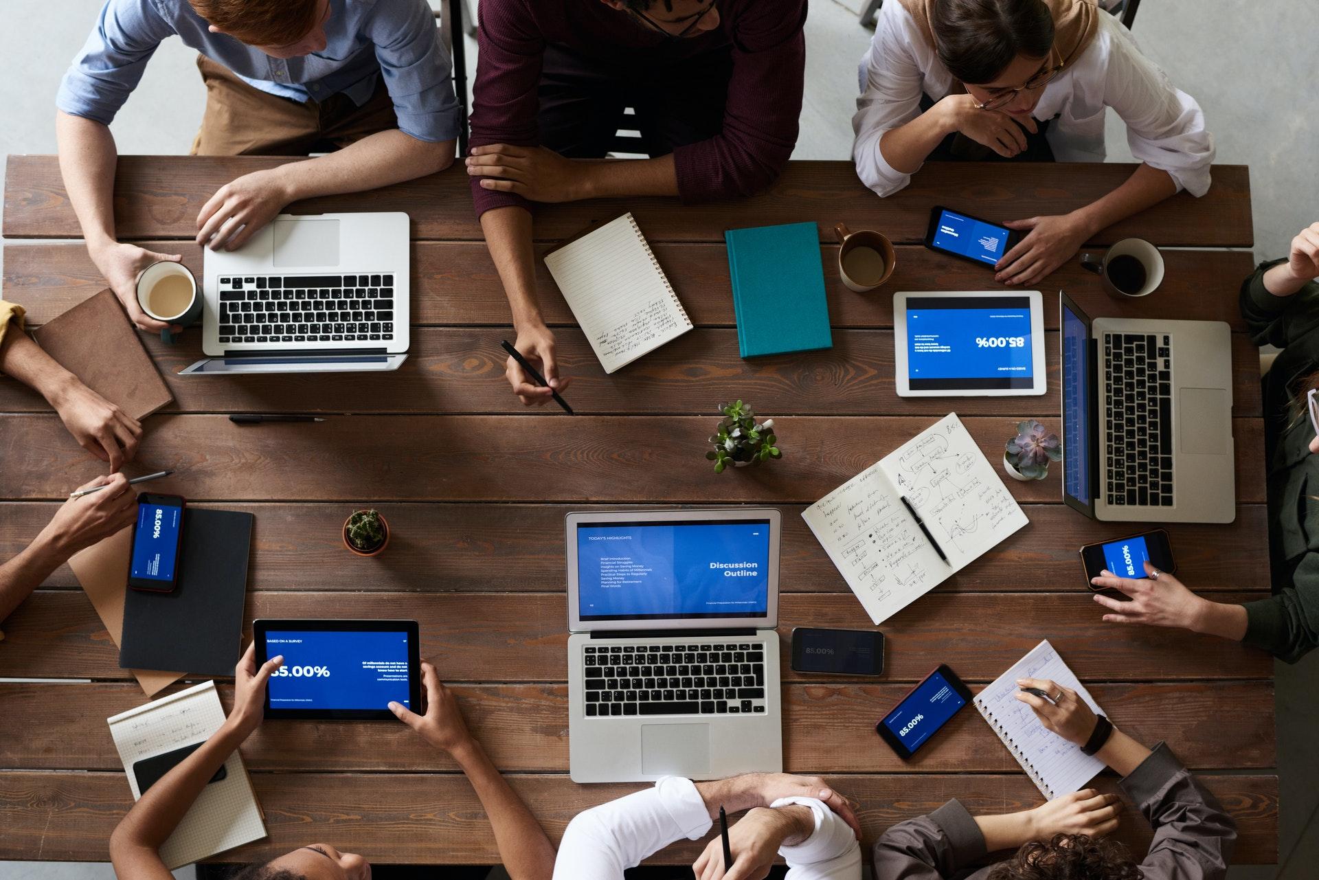 Visto de cima, vemos várias pessoas reunias ao redor de uma mesa; sobre ela vários computadores, agendas, tablets etc. (imagem ilustrativa).