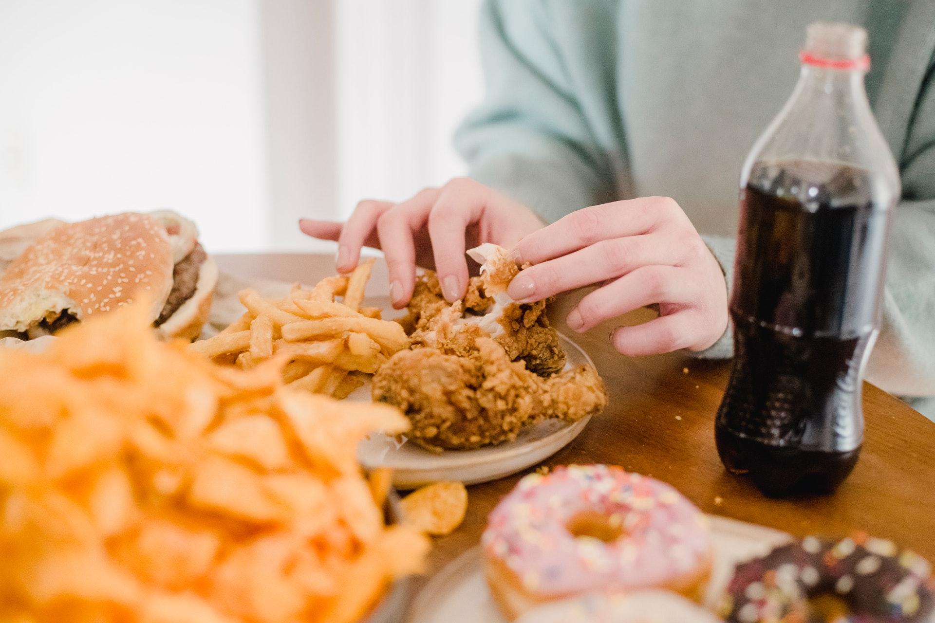 Vemos uma pessoa comendo frango frito (imagem ilustrativa).