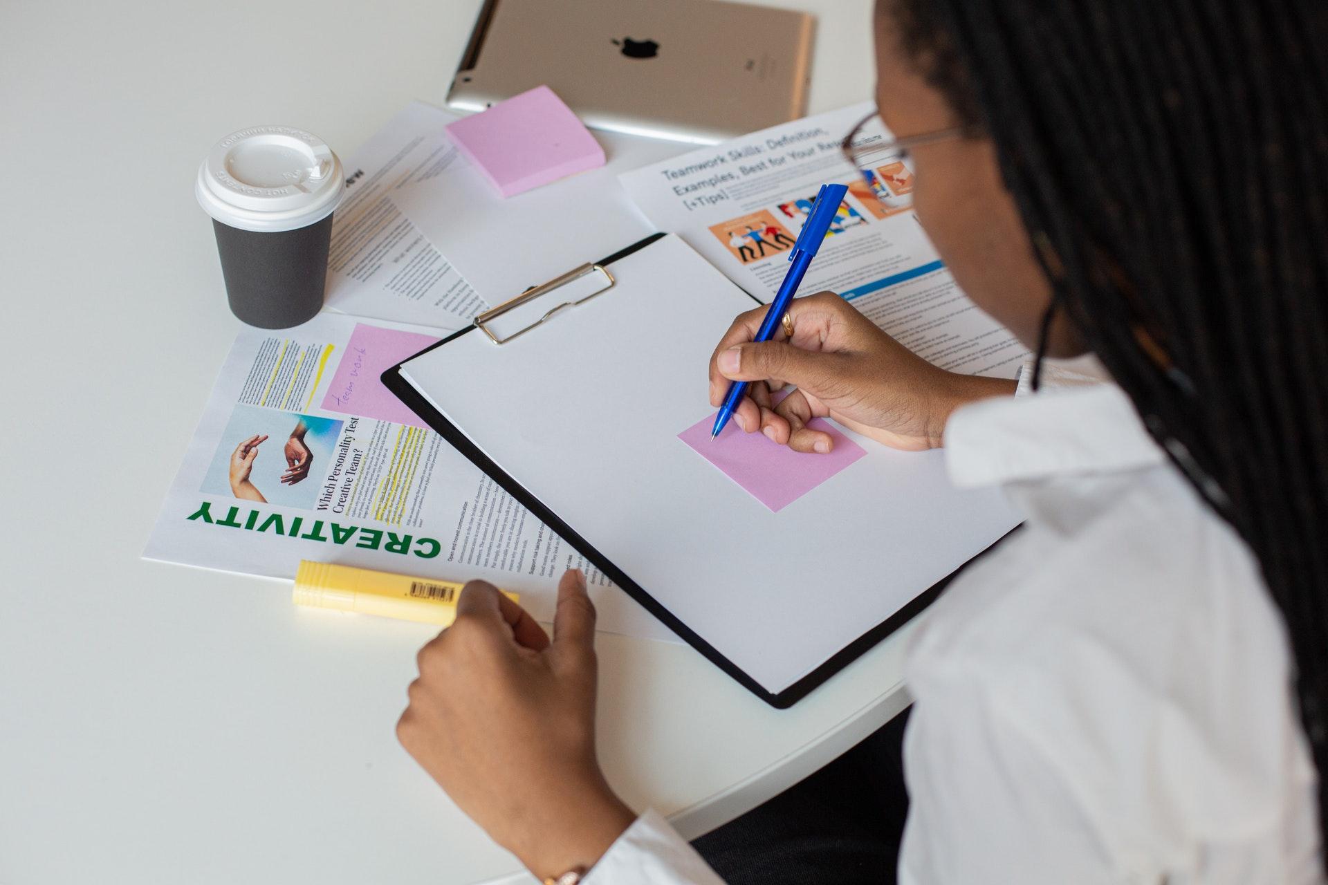 Imagem de uma mulher escrevendo em um papel em uma prancheta. Imagem ilustrativa texto negócios lucrativos com pouco dinheiro.